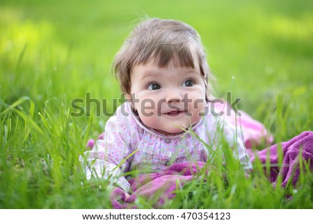Small cute baby girl with pretty face and funny eyes sitting on green grass outdoor on natural background