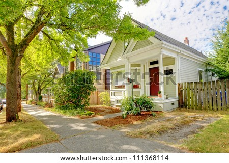 Small cute craftsman American house with green and white and red door. - stock photo