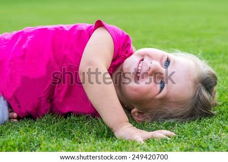 Small cute European girl posing lying down in the green grass.
