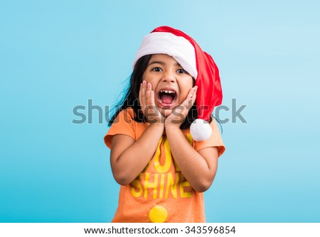 small cute indian girl with christmas hat, thinking, indian girl and christmas, christmas and india, indian kids and christmas, indian kids celebrating christmas, asian girl and christmas, thinking - stock photo
