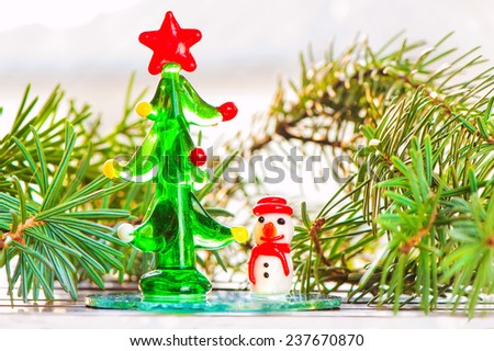 Small decoration - glass snowman-toy and christmas tree. Indoors close-up. - stock photo