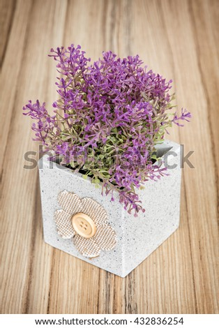 Small decorative potted plant on the wooden background. Home decoration. Beautiful house plant. Artificial flower. Vertical composition. Gardening theme. - stock photo