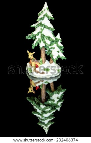 Small deer and tree with snow on the ground - stock photo
