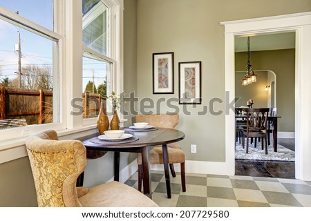 Small dining area in kitchen room. View of served round table with brown chairs