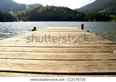 Small dock leading in a lake in the Alps - stock photo