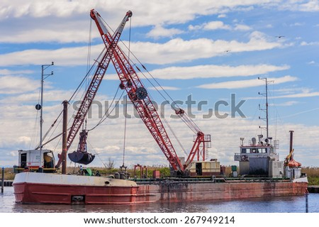 Small dredge marine, which is cleaning a navigation channel - stock photo