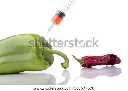 small dry paprika and a big fresh green paprika with a syringe - stock photo