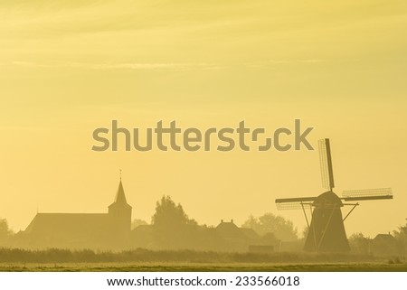 Small Dutch town with a windmill and a church at sunrise. - stock photo
