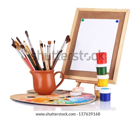 Small easel with sheet of paper and art supplies isolated on white - stock photo