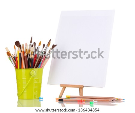 Small easel with sheet of paper with art supplies isolated on white - stock photo