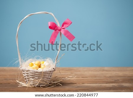 Small Easter eggs in a basket with the ribbon.