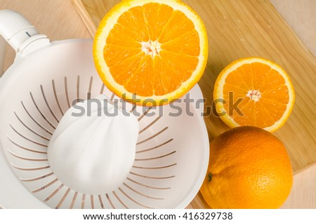 Small electric juicer on a wooden kitchen table - stock photo
