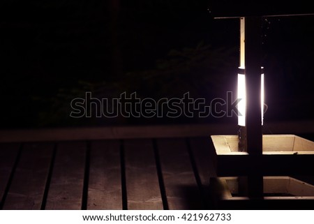 Small electric outdoor lantern glowing at night close up