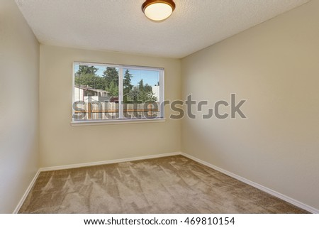 Small empty room interior with beige carpet floor and one  window. Northwest, USA