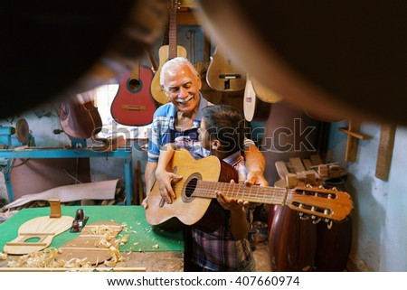 Small family business and traditions: old grandpa with grandson in lute maker shop. The senior artisan gives teaches how to play classic guitar to the boy, who plays his first musical notes  - stock photo