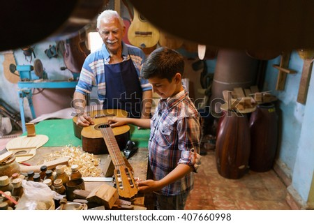 Small family business and traditions: old grandpa with grandson in lute maker shop. The senior artisan teaches how to tune a classic guitar to the boy, holding a diapason. - stock photo