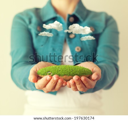 Small fantastic island in women's hands. - stock photo