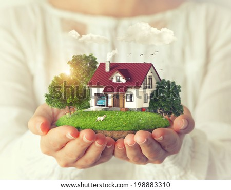 Small fantastic island with a house and backyard in women's hands. - stock photo