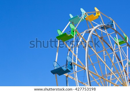 Small Ferris Wheel Ride at an Amusement Park on a Clear Sky Background - stock photo