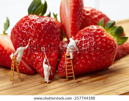 Small figures of painters paint strawberries - stock photo