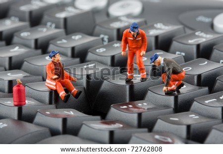 Small figurines of workers repairing computer keyboard - stock photo