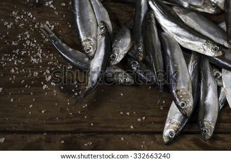 Small fish sprat and salt on a wooden board closeup top view
