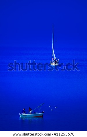 Small fishing boat and sailing boat meet in the blue sea. - stock photo