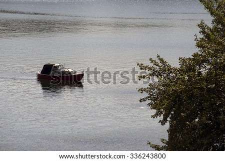 Small fishing boat close to tree and forest. Little Belt in Denmark. - stock photo