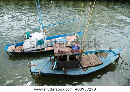 Small fishing boat floating at the jetty on the sea. - stock photo