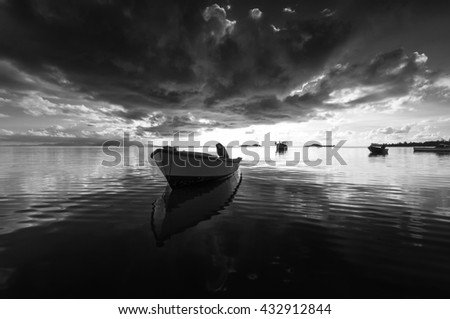 Small fishing boat floating on the ocean in beautiful sunset reflected in the water Seychelles Island, black and white image