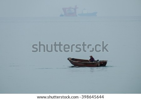 Small fishing boat in foggy early morning.