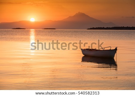 Small fishing boat in the calm Greek bay at sunrise