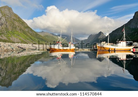 Small fishing boat in the harbor of the fjord - stock photo