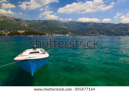 Small fishing boat is moored at the coast in transparent water Adriatic Sea - stock photo