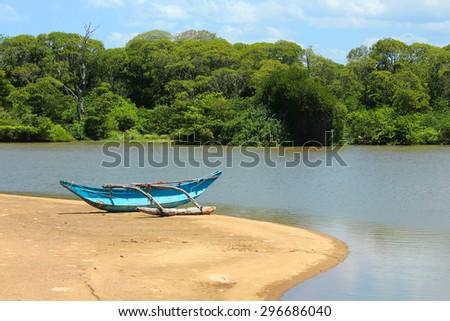 Small fishing boat on the beach at the lagoon, Sri Lanka - stock photo
