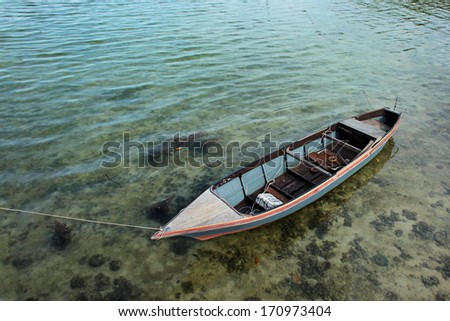 Small fishing boat on the sea water - stock photo