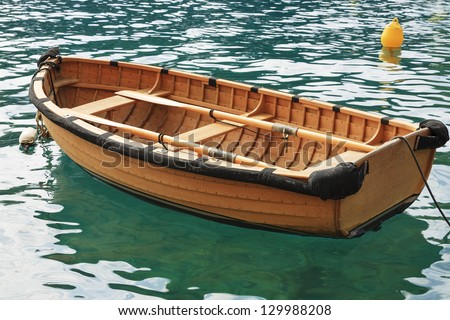 Small fishing boat on the sea water in a secluded bay - stock photo