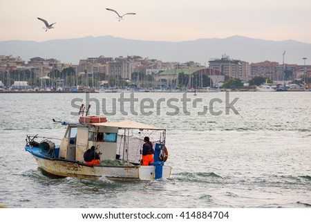 Small fishing boat that returns to the harbor at dawn - stock photo