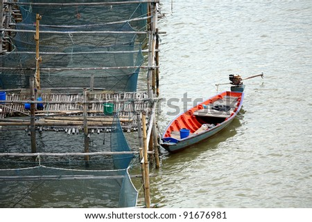 Small fishing boat with a rope at the fish cages