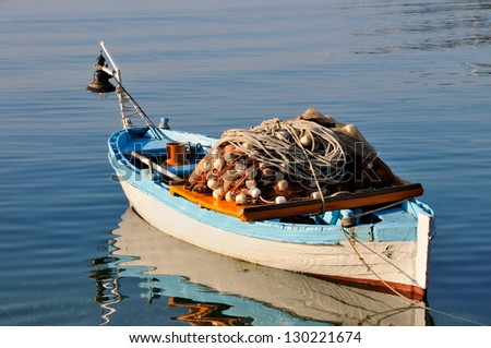 Small fishing boat with fishing net and equipment - stock photo