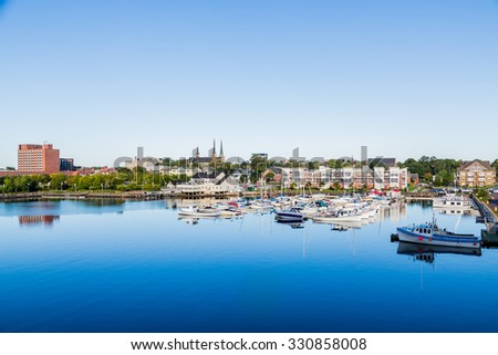 Small fishing boats in a calm blue harbor on Prince Edward Island in Canada - stock photo