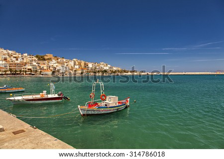 Small fishing boats in crystal clear waters. Sitia, Crete.  - stock photo