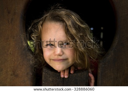 Small five year old girl poking head through window of playground equipment. - stock photo