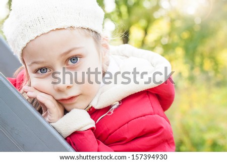 Small five years old caucasian girl in warm clothes - close up autumn outdoor portrait - childhood - stock photo