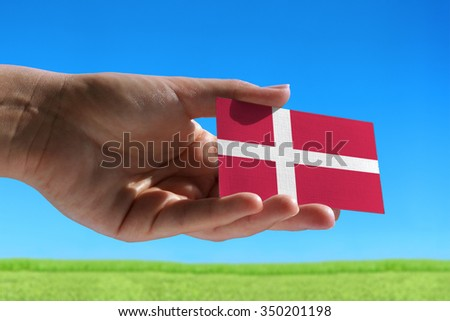 Small flag of Denmark against beautiful landscape with grass - stock photo