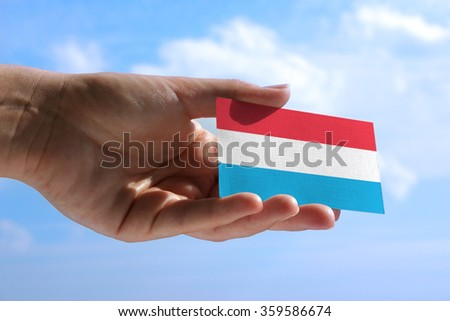 Small flag of Luxembourg, cumulus clouds in background - stock photo