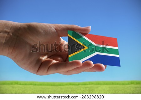 Small flag of Republic of South Africa against beautiful landscape with grass - stock photo