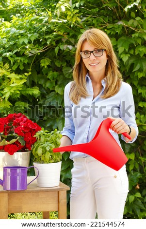 Small flower shop owner standing and holding cans while working in her store. Small business.  - stock photo