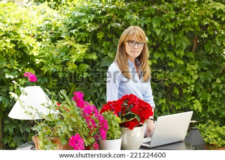 Small flower shop owner working on laptop, while standing at desk in her store.  Small business.  - stock photo