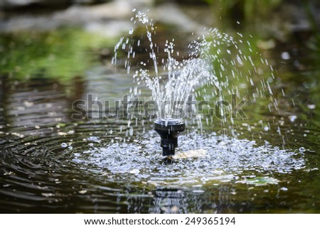 Small fountain in the pond - stock photo